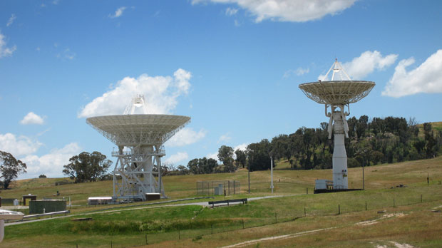 Two antennas in a field with blue sky. Left antenna Deep Space Station 34, right antenna Deep Space Sation 33