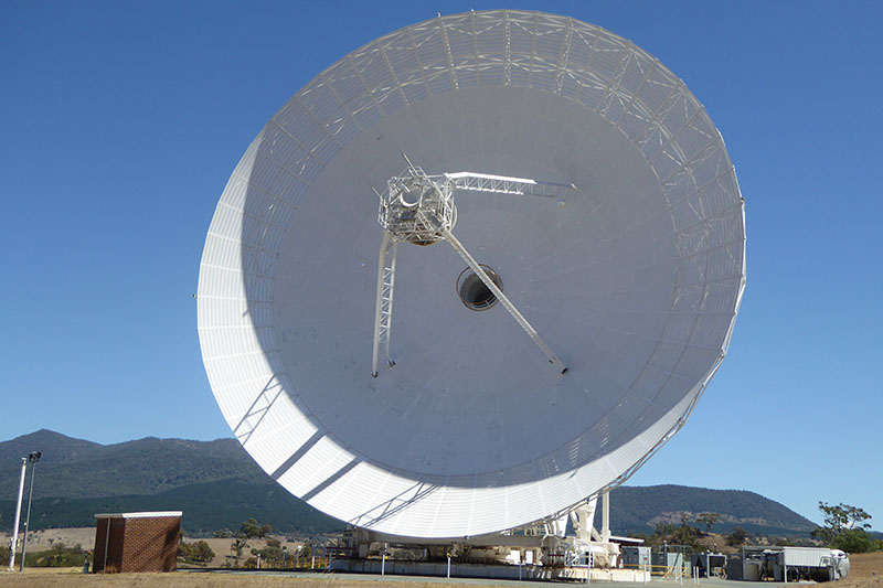Front view of DSS34 showing the round dish, hole in the centre of the dish and quadrapod legs