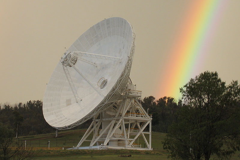 Angled view of DSS34 showing part of the support structure and a rainbow in the background