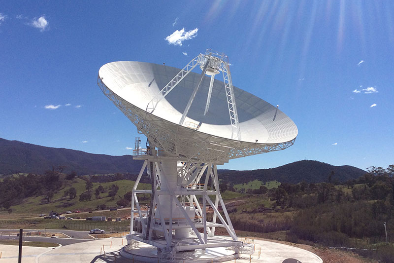 DSS35 on an angle, showing the quadropod legs and rays of sunlight on the right, hills in the background