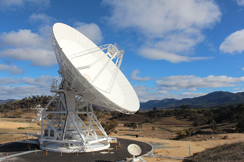 DSS36 on left, on an angle facing to the right. Blue sky with clouds, hills in the background, tiny dish to the right
