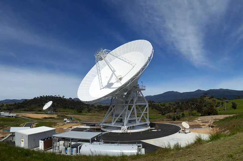 Wider shot showing DSS36 in the centre, on an angle facing to the left. DSS45 in the backgroun to the left and tiny dish to the right. Blue sky with clouds and hills in the background