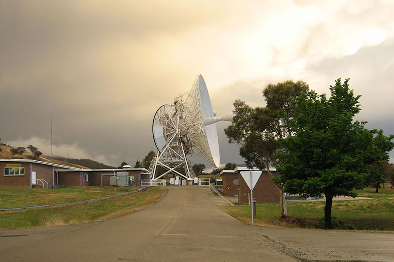 Deep Space Station 46 on an angle at the end of a road with stormy clouds and buildings surrounding it