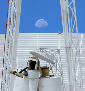 Feed horns, quad legs and dish of Deep Space Station 43 with the Moon above the dish surface
