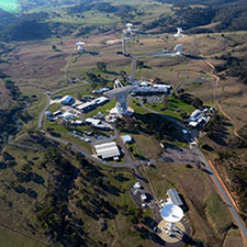 Aerial view of the Canberra Deep Space Communication Complex, showing six antennas and buildings.