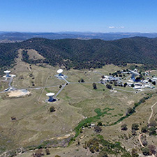 Side on aerieal view of the Canberra Deep Space Communication Complex, showing six antennas, buildings, hills and the blue sky in the background.
