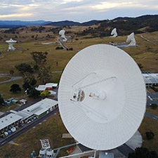 Low aerial view of the Canberra Deep Space Communication Complex, with DSS43 large in the foreground on an angle, and four antennas in the background, along with hills and cloudy sky.
