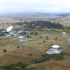 Side on aerial view of the canberra Deep Space Communication Complex, with hills and misty cloud in the background.