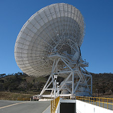 The antenna Deep Space Station 34 facing away from the camera, showing the driveway that leads under the antenna, hills and blue sky in the background.