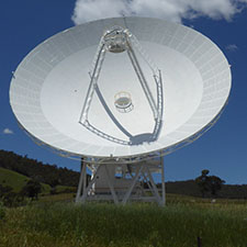 Deep Space Station 35 showing the dish, quad legs and subreflector, green grass in front, hills behind and a blue sky with clouds.