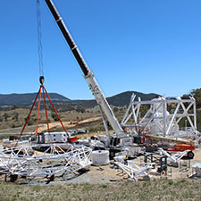 Sections of the pedestal structure of Deep Space Station 35 on the ground with a crane attached to part of it, hills and blue sky in the background.