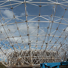 The ribs of the dish structure with no panels covering them, blue sky with clouds behind.