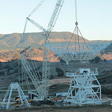 A crane lifting the dish for Deep Space Station 35 on to its pedestal structure. Quad legs sitting on the left, hills behind being lit up by sunrise.