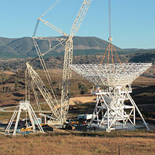 Crane attached to the dish of Deep Space Station 35 with the dish now sitting on the pedestal. Blue sky and hills behind, a yellow glow on the ground from the rising Sun.
