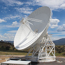 Deep Space Station 36 on an angle showing the surface of the dish, blue sky with clouds and hills in the background.