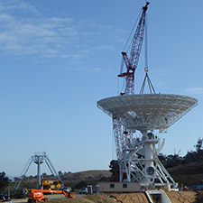 Crane lowering the dish of Deep Space Station 36 on to the pedestal structure. Quad legs sitting to the left of the antenna with blue sky behind.