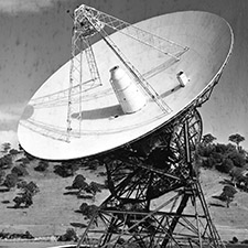 Black and white photo of antenna Deep Space Station 42 on an angle showing the dish, receiving cone and quad legs. Trees and hills in the background.