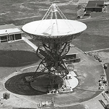 Aerial black and white photo of antenna Deep Space Station 42 facing straight up, with some buildings around it.