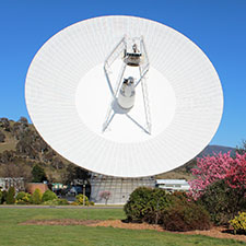 The antenna Deep Space Station 43 facing towards, showing the cone structure int eh middle and the quad legs. Grass and bushes in front with spring colours and blue sky behind.