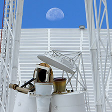 Feed horns of deep space station 43 in the foreground with part of the a leg on other side from the quad structure, the edge of the dish in the background with blue sky and a half Moon above it.