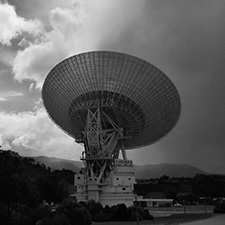 Black and white moody photo of Deep Space Station 43 antenna facing away with varying shades of cloud in the background.