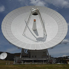Deep Space Station 45 on an angle, showing the dish surface and receiver structure, DSS-34 in the far background.