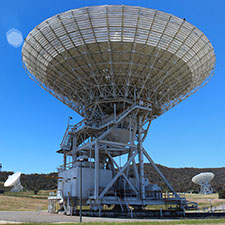 Antenna Deep Space Station 45 facing up with a very blue sky and two other antennas in the background.