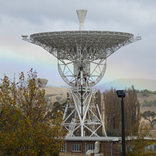 Antenna Deep Space Station 46 facing straight up with trees in the foreground, cloudy sky and a rainbow in the background.
