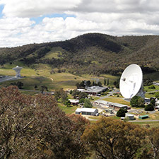View of the Canberra Deep Space Communication Complex from a hill showing trees in the foreground, and the antennas and hills in the background. A mostly cloudy sky.
