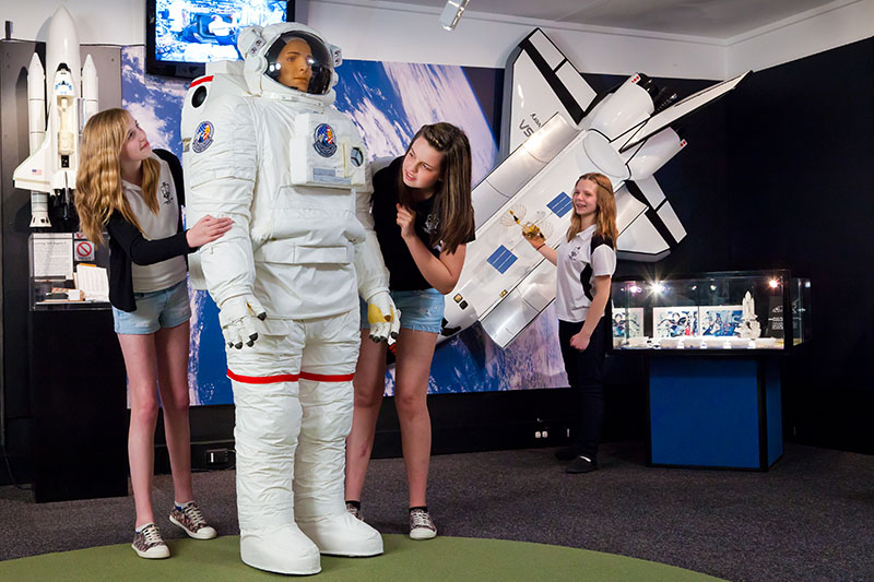 Three teenage girls looking at a model of a spacesuit while another girl stands next to a model of the space shuttle on the wall