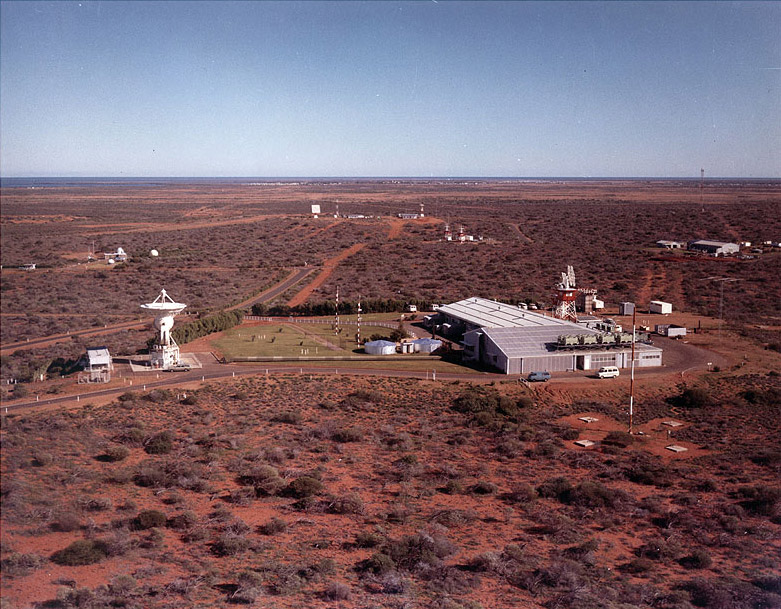 Aerial view of Carnarvon showing red dirt with plants, several buildings, roads and an antenna.