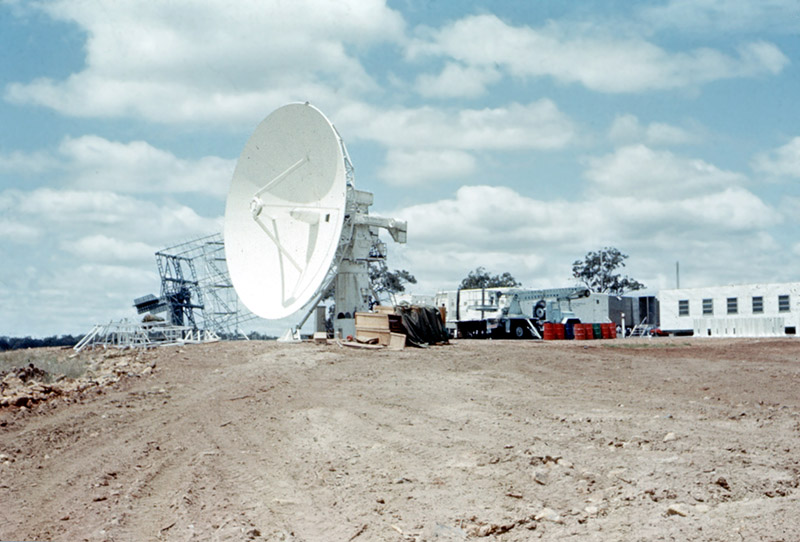 An antenna on an angle with dirt in front of it and trucks and building beside it, blue sky with clouds behind.