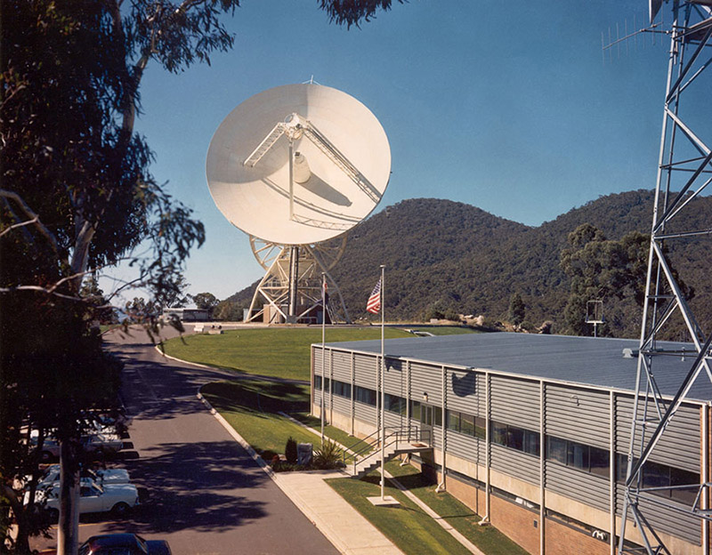 Side of a building with a road running beside it and an antenna in the background with the dish facing towards the camera and hills, Honeysuckle Creek