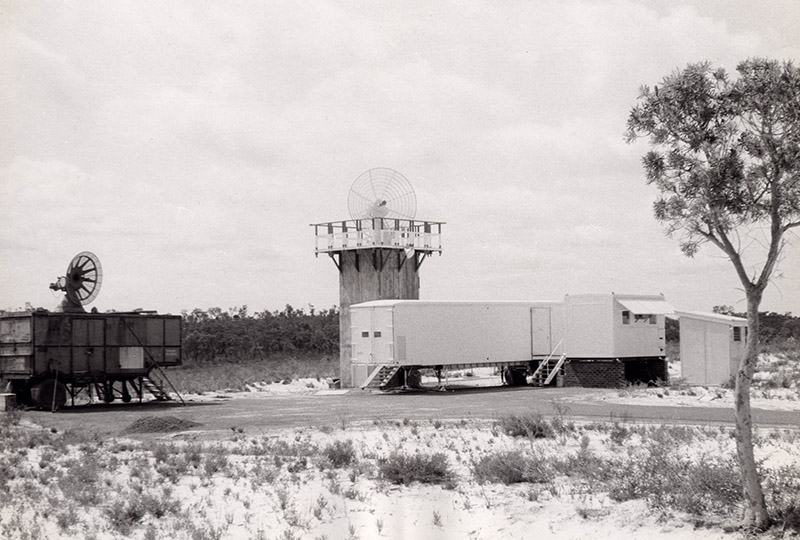 Black and white photo showing sand, trees, demountable type buildings and some small antenna dishes.