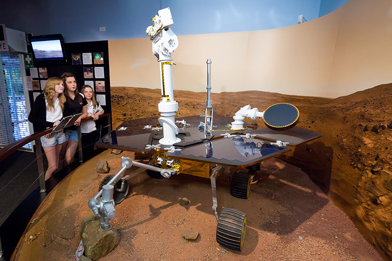 Three teenage girls looking at a model of the Mars Exploration Rovers
