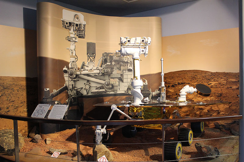 Model of the Mars Exploration Rovers in the foreground, drawing of Mars Science Laboratory in the back